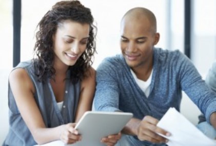 Multi Ethnic Female & Male looking at tablet together