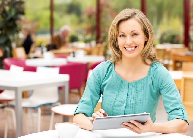 Woman using tablet sitting in cafe