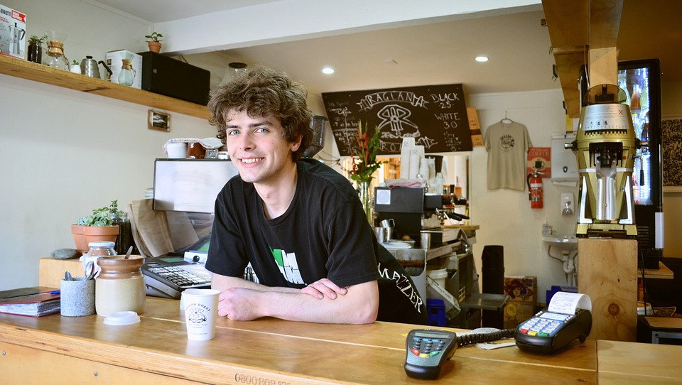 Young happy waiter at counter