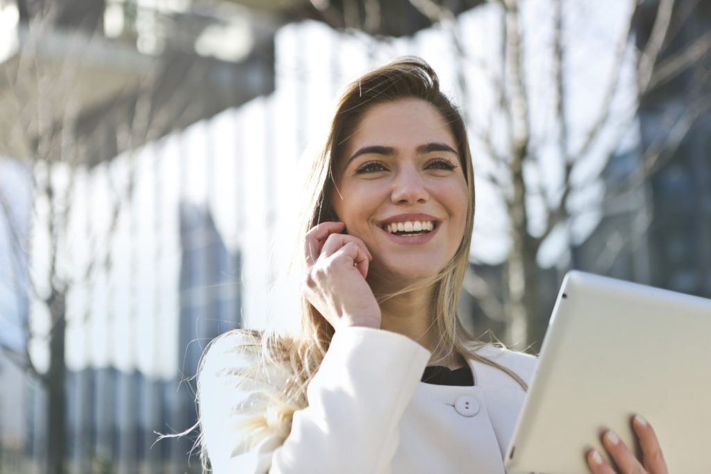 Smiling Woman-Happy Girl holding tablet talking on cell phone