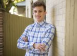 Smiling young man in plaid shirt standing against brick wall in backyard