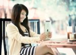 Young smiling woman sitting outside looking at tablet_female