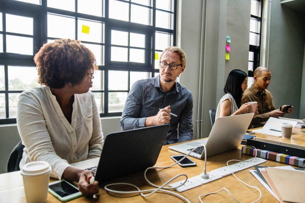 Men and women working at desks on laptops together