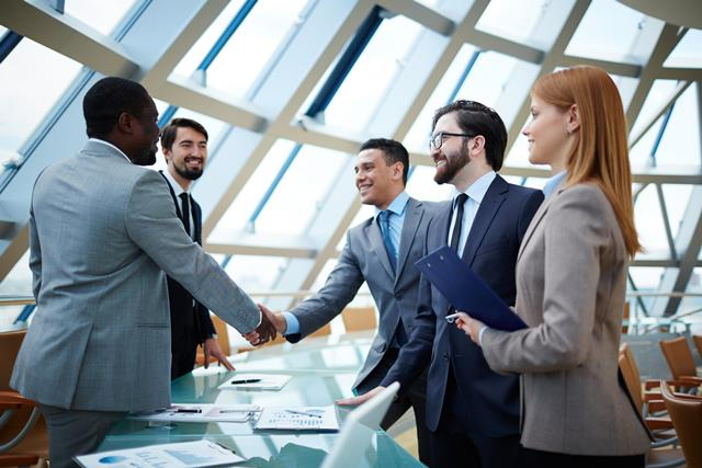 Two businessmen shaking hands surrounded by female and male coworkers