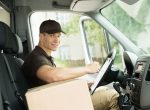 Delivery driver with package sitting in vehicle